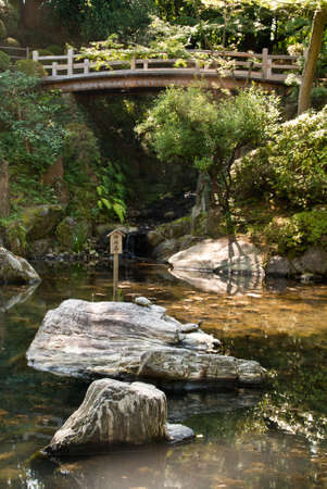 A Japanese ornamental pond with arched wooden bridge in the background Stock Photo