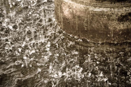 Closeup of a fountain spraying into its reservoir