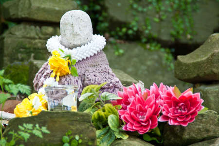 Clothed Buddhist statue with pink and yellow flowers