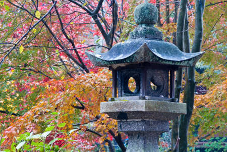 Stone lantern shot against a colorful background of fall foliage Stock Photo