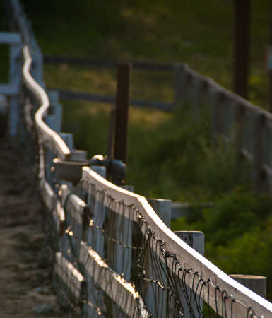A highlighted railing fence cuts diagonally across the frame