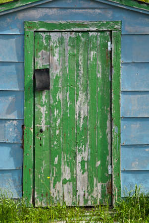 blue door: Closeup of an old green-doored fishing shed
