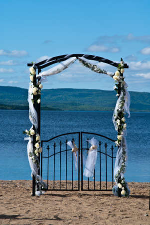 Flower covered wedding arch on a beach photo