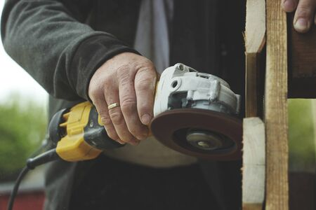 Man creating zero waste furniture, hobby, lockdown, garage, grinding. Banque d'images