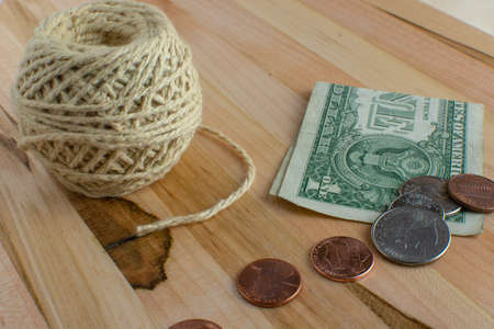 US pocket change on top of a folded dollar bill next to a ball of string placed on a wooden table.