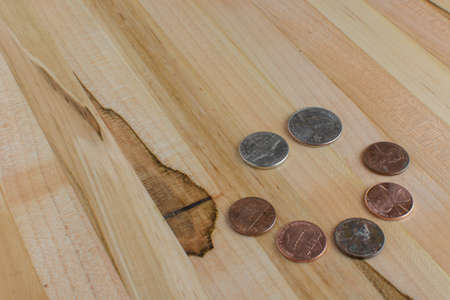 US pocket change conceptual art of a happy face arranged on a wooden table. Stock Photo