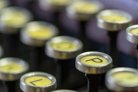 A closeup of the keys on an antique typewriter focusing on the letter P.