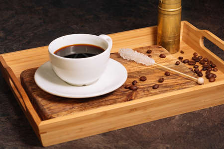 Hot coffee in white cup and white sugar stick on a wooden tray. Low key. Black background. Breakfast concept