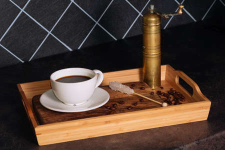 Hot coffee in white cup and white sugar stick on a wooden tray. Low key. Black background. Breakfast concept 版權商用圖片