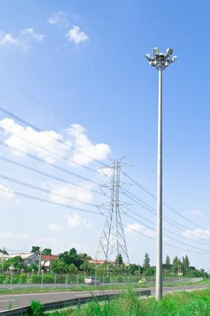 Steel electricity pylon on bright blue sky.