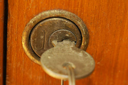 key cabinet: Old antique key in lock of wooden cabinet Stock Photo