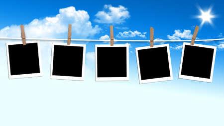 Fotografie in bianco appeso su una clothesline contro un cielo di giorno d'estate