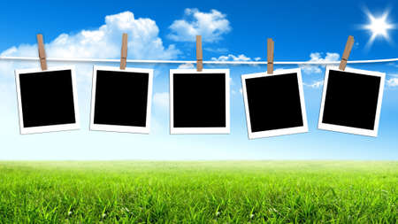 Blank photographs hanging on a clothesline against a sky summer day photo