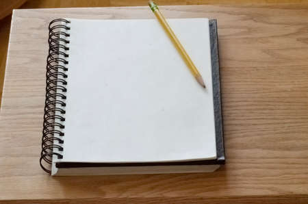 Angled sketch pad and pencil on top of pad