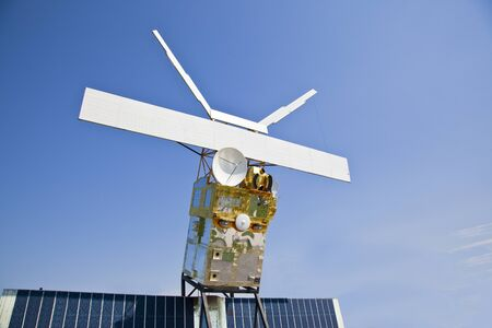 Old satellite under blue background