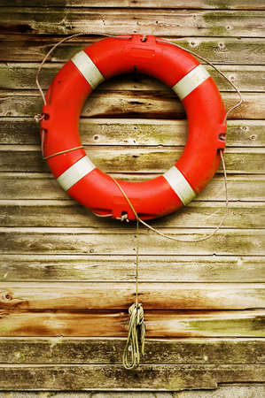 Lifebouy hanging on wooden wall.