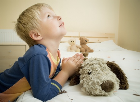 Little boy prays in the bedroom by the bed.