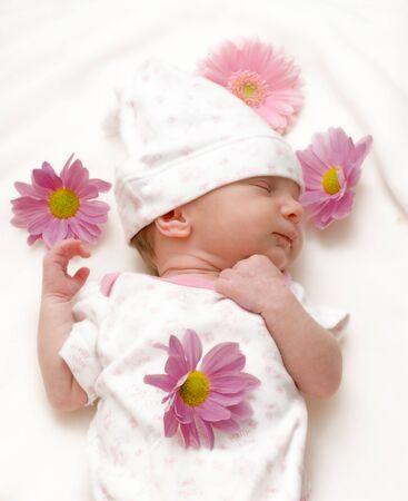 Dormir infantil, bebé, niña con margaritas en manta blanca