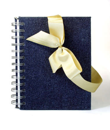 The gift notebook decorated with a gold ribbon bow. photo