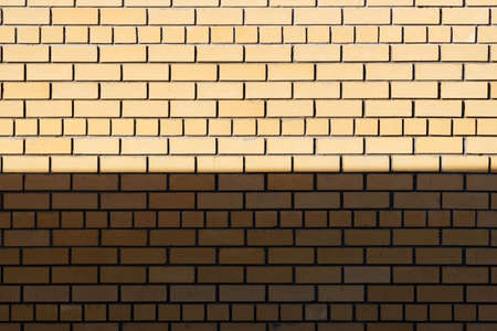 terminator: Light terminator on the yellow brick wall. Stock Photo