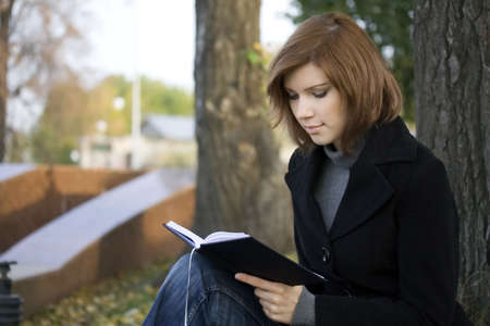 Beautiful girl reading book in the city park. Stock Photo - 3813693