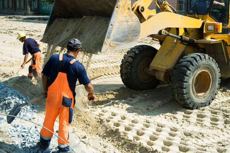 Worker and road loader. Stock Photo