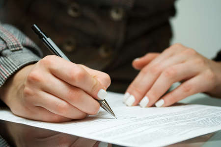 filling out: Businesswoman filling out contract.