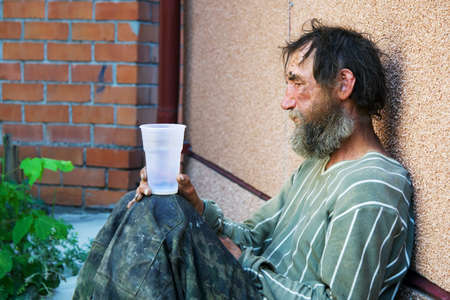 old beggar: Homeless poor alcoholic in depression. Stock Photo
