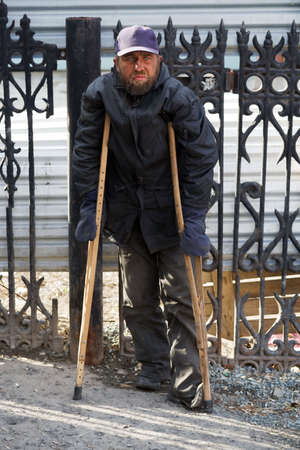 old beggar: Disabled homeless man walking on crutches.