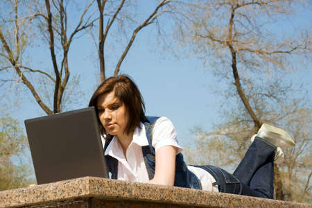 Young woman working on laptop in the city park. photo