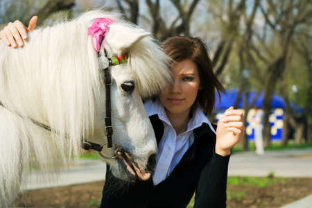 pony girl: Young woman with a white pony. Stock Photo