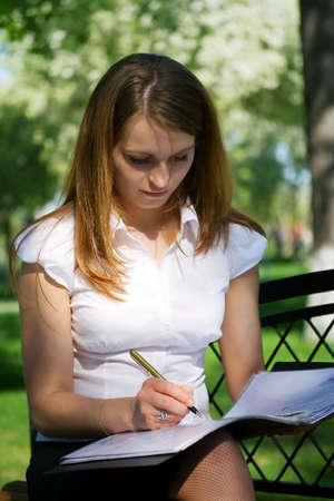 Young businesswoman working with financial reports in the park. Stock Photo - 5188850