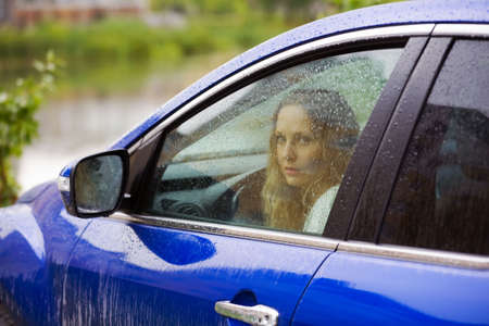 Sad young woman looking through the window with a rain drops. Stock Photo - 5390834