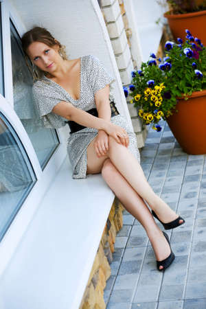 Beautiful young woman sitting on the window of cafe. Stock Photo - 5423677