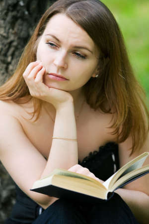 Thoughtful young woman reading on nature. photo