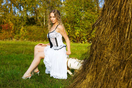 Young woman sitting on the log against a haystack. photo