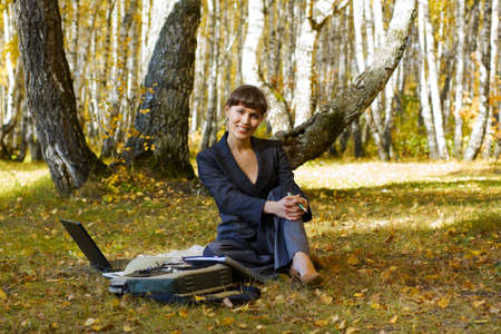 Young businesswoman using laptop in the birch forest. photo