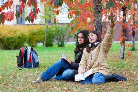 Two young teenage students reading in the park. photo