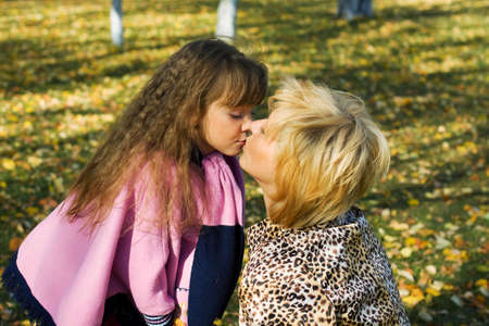 Mother and daughter kissing in the park. photo