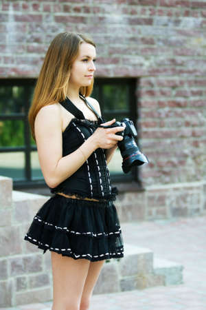 Young woman holding a digital photo camera. photo