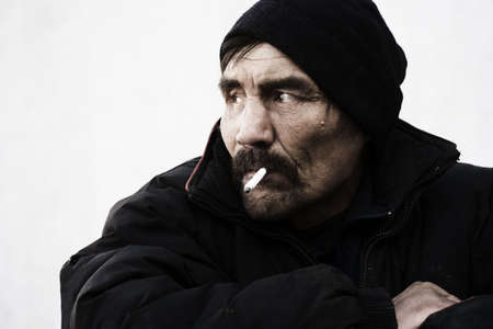 tramp: Smoking homeless. Stock Photo