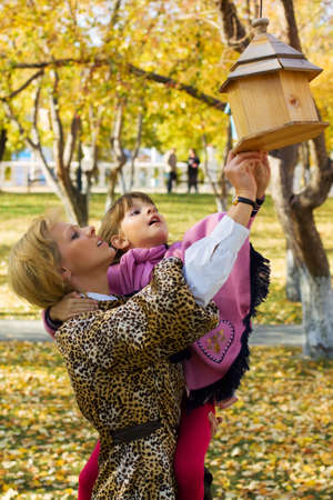 Mother and daughter looking in a birdhouse. photo