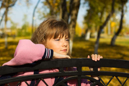 Thoughtful little girl leaning on a bench. photo