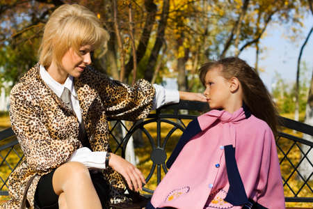 mother on bench: Mother and daughter sitting on a bench.