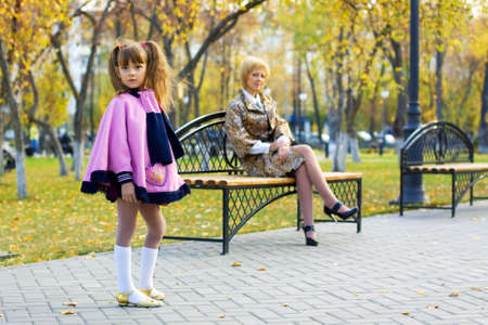 mother on bench: Pretty little girl with her mum in an autumn park.