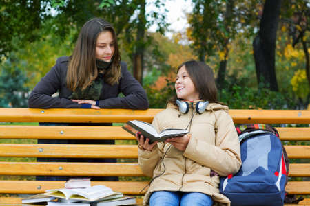 Two young teenage friends reading in the park. photo