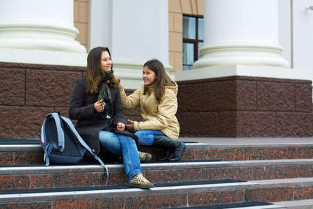 Two young teenage students sitting on the stairs. photo
