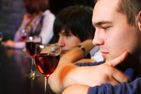 Los hombres j�venes que beber vino tinto en una barra de contador.