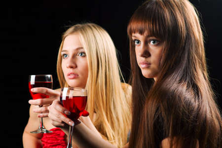 Two young women drinking red wine in a bar. Stock Photo - 6090390