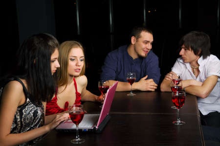 Young friends drinking red wine in a bar. photo